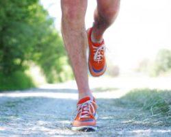 Mann läuft einen Feldweg entlang