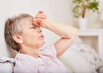 Eine erschöpfte ältere Frau fasst sich an die Stirn