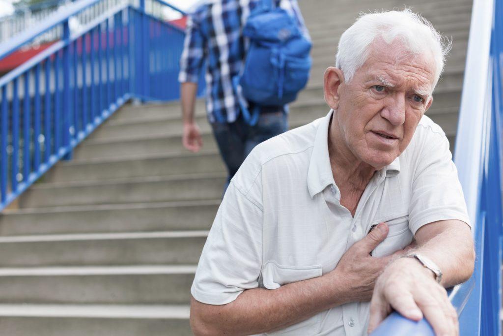 Ein älterer Mann auf einer Treppe fasst sich ans Herz