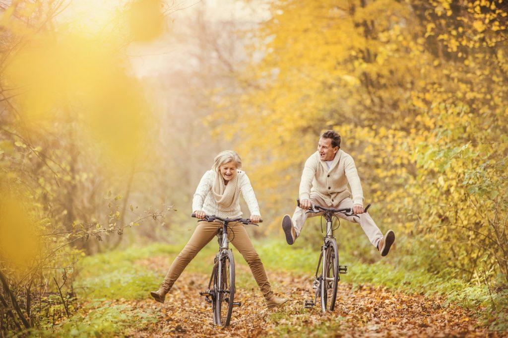 Seniorenpaar radelt durch den Herbstwald