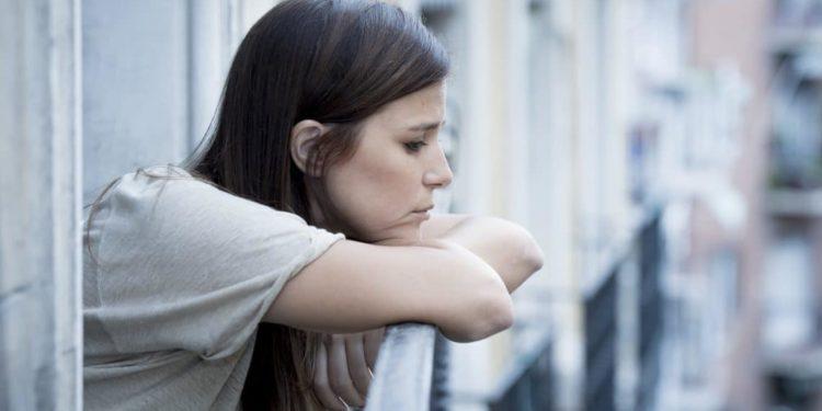 Eine junge, unglücklich aussehende Frau lehnt sich auf ein Balkongeländer