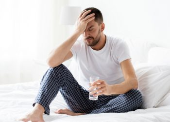 Mann sitzt im Bett und fasst sich mit einer Hand an den schmerzenden Kopf und hält in der anderen Hand ein Glas mit Wasser