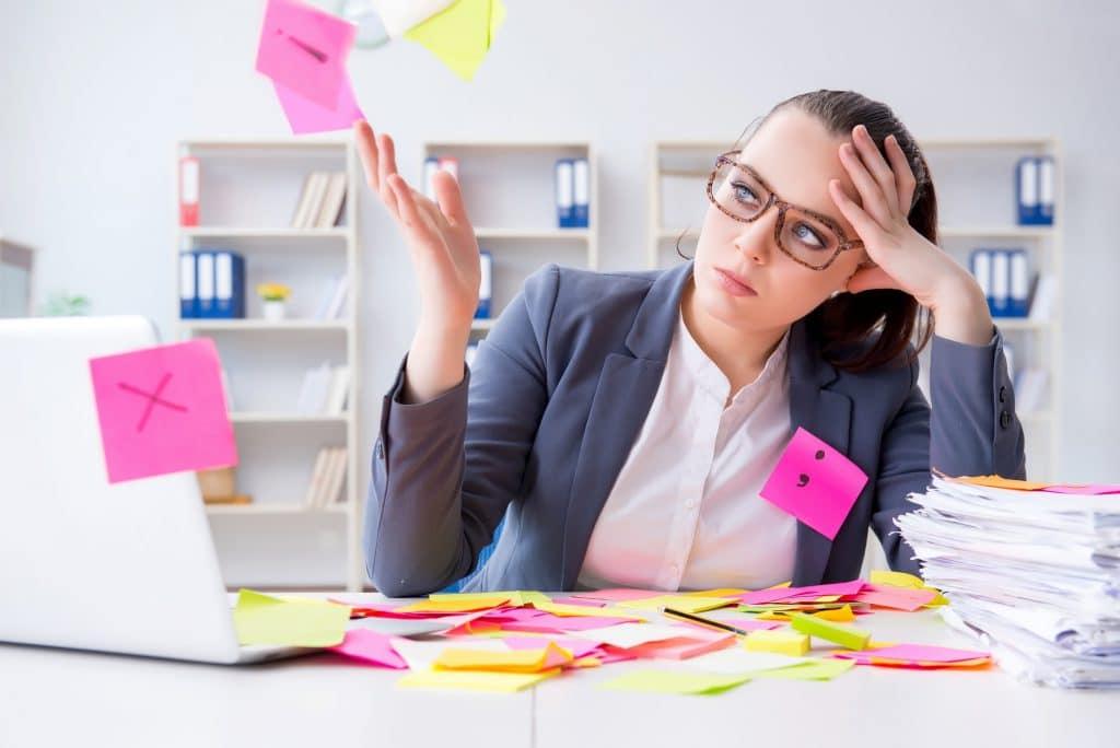 Genervte Frau am Schreibtisch mit Post-it-Zetteln