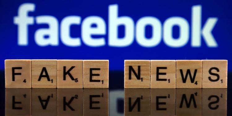 Scrabble Steine mit den Begriffen Fake und News vor dem Schriftzug von Facebook