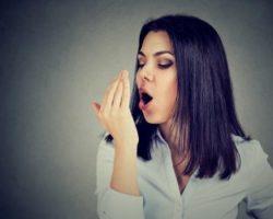 Frau hält sich Hand vor den Mund um ihren Atemgeruch zu testen