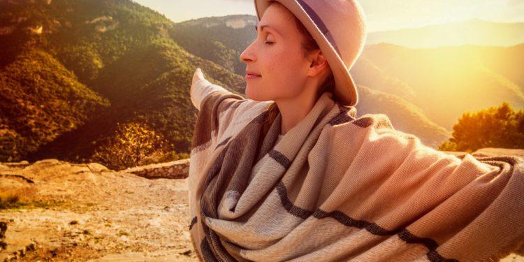 Frau in bergiger Landschaft streckt ihre Arme aus