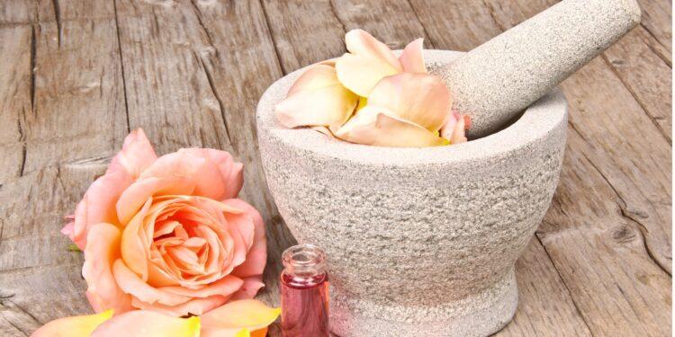 Ein Mörser mit Rosenblättern gefüllt sowie einige lose Rosenblätter und ein Fläschchen Rosenöl auf einem Holztisch.