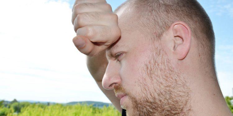 Mann fasst sich an die Stirn.