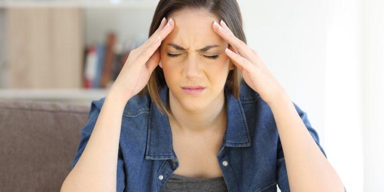 Junge Frau wird von Kopfschmerzen geplagt