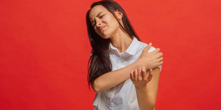 Frau fasst sich an die schmerzende Schulter.