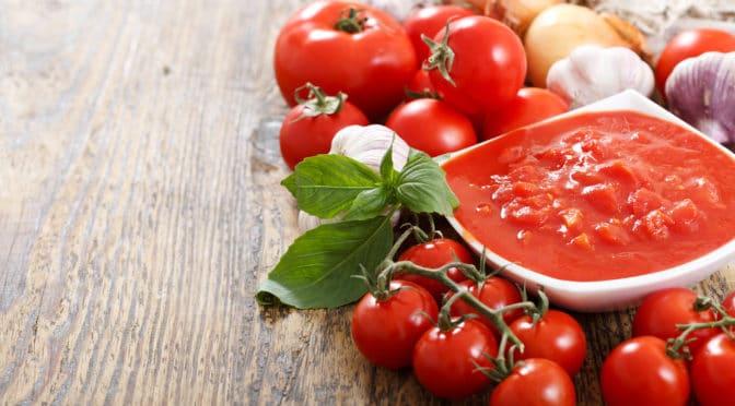 Frische Tomaten, Zwiebeln, Knoblauch und eine daraus zubereitete Tomatensoße