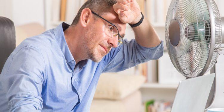 Mann am Schreibtisch leidet unter der Hitze