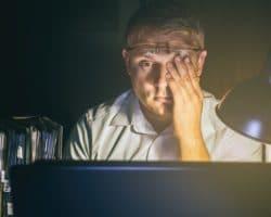 Mann reibt sich vor dem Computer seine müden Augen