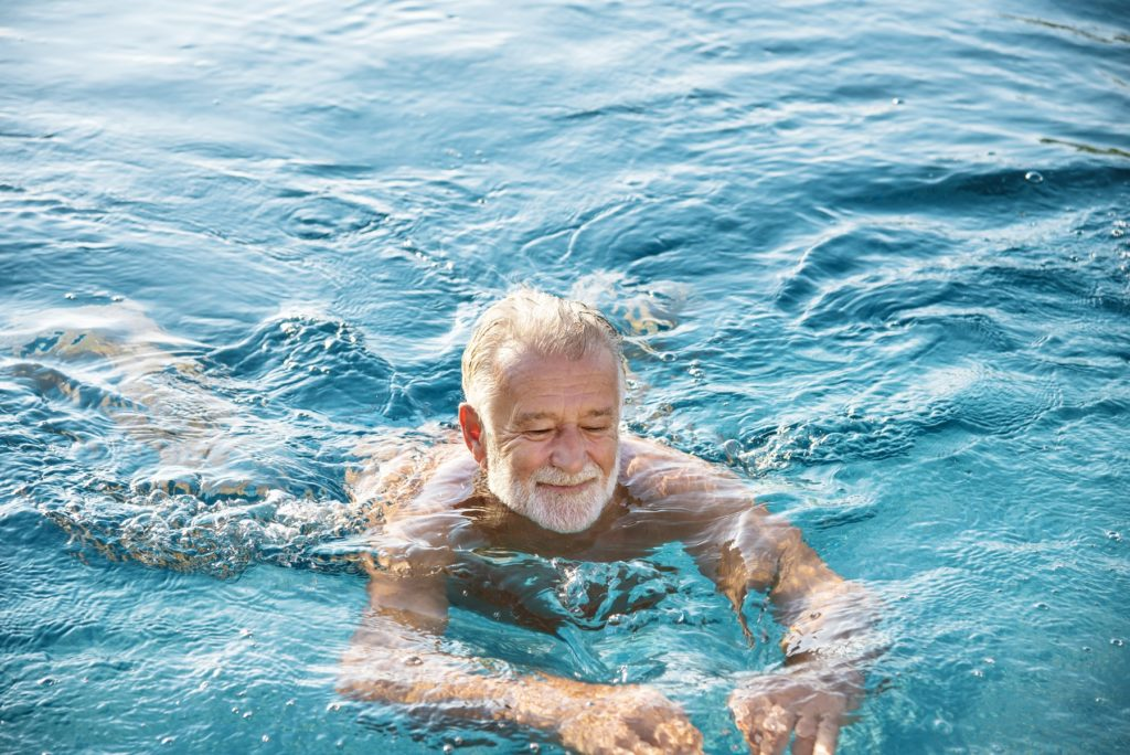 Älterer Mann schwimmt in einem Gewässer