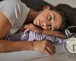 Frau liegt mitten in der Nacht wach im Bett und sieht auf den Wecker