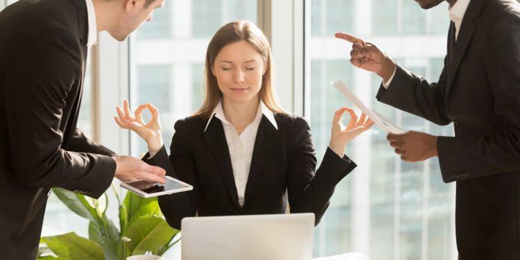 Eine Frau sitzt im Büro und meditiert, während zwei Männer auf sie einreden.