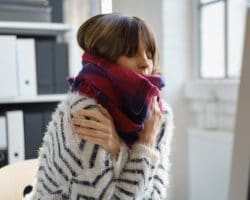 Eine erkältete Frau wärmt sich mit einem Schal und ihren Händen