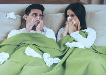 Eine Frau und ein Mann liegen im Bett und schnäuzen sich die Nase