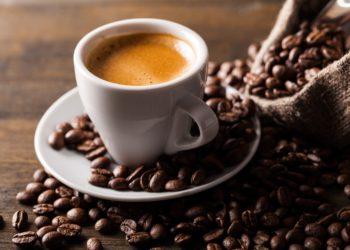 Tasse Kaffee mit Kaffeebohnen daneben.