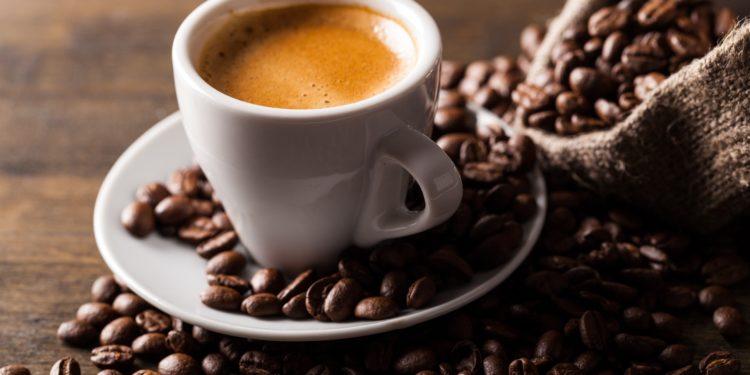 Taza de café con granos de café a su lado.