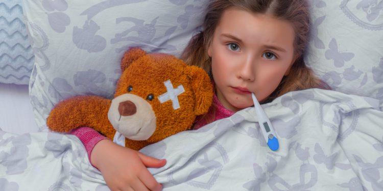 Mädchen liegt mit Teddy im Bett und hat ein Fieberthermometer im Mund