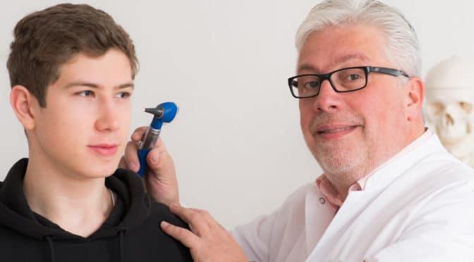 Arzt untersucht das Ohr eines Jugendlichen