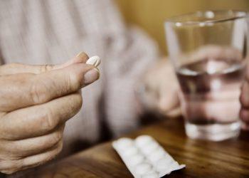 Ältere Person nimmt eine Tablette ein