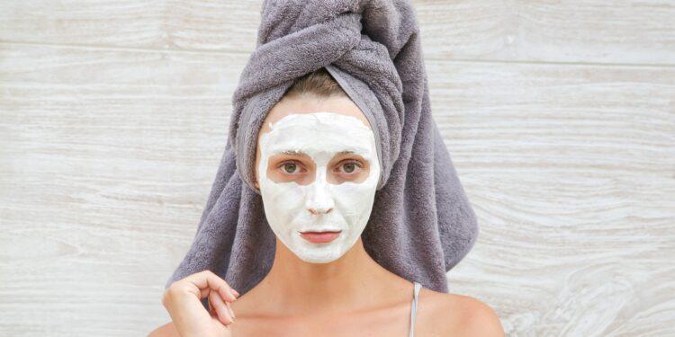 Frau mit weißer Gesichtsmaske und um die Haare gewickeltem Handtuch.