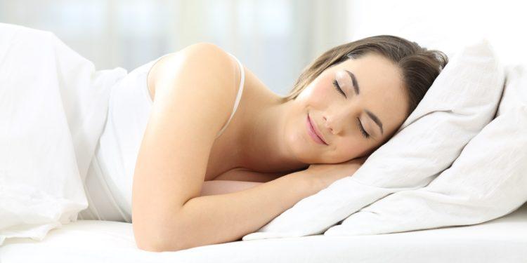 Glücklich aussehende Frau schläft in einem Bett