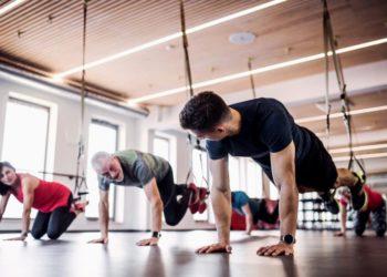 Mehrere Senioren trainieren im Fitnessstudio mit einem jungen Trainer