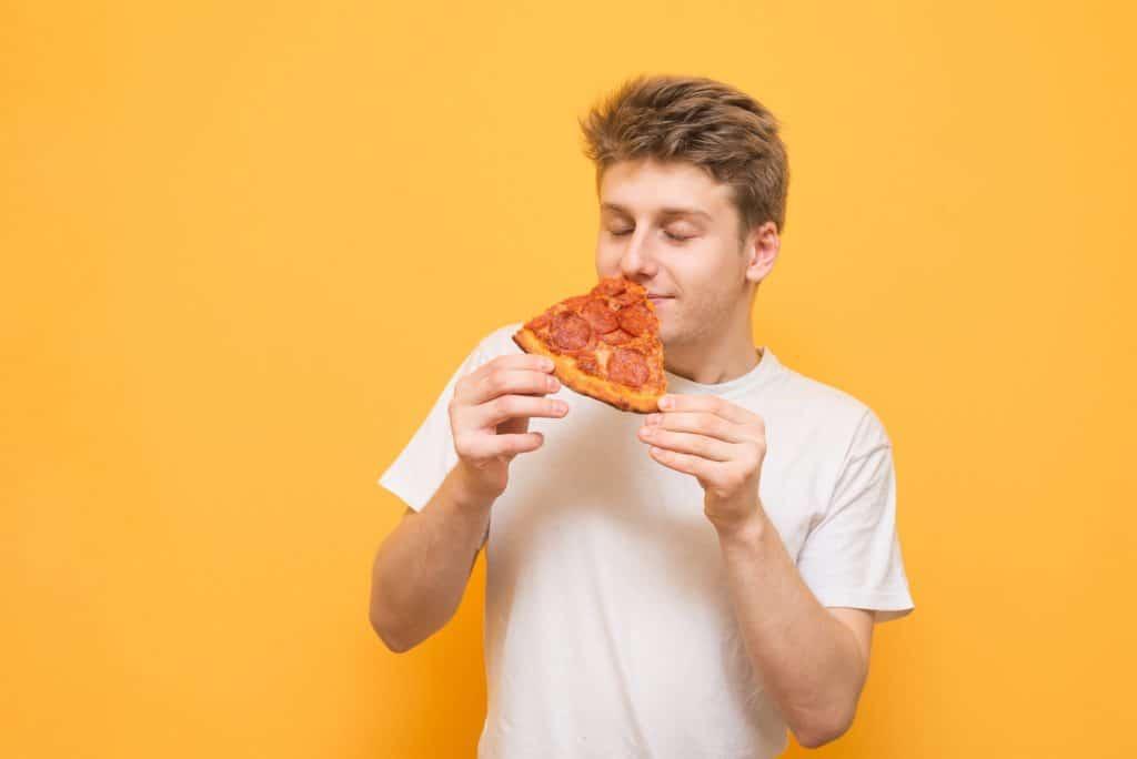 Junger Mann riecht an einem Stück Pizza