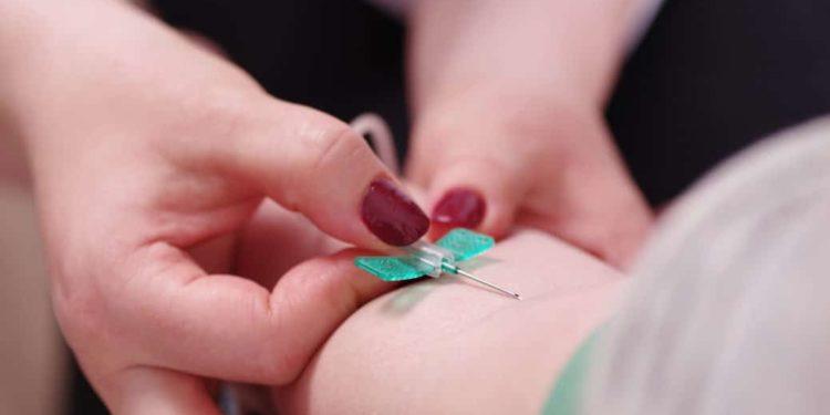 Frau nimmt einem Patienten Blut ab