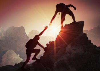 Ein Bergsteiger reicht einem anderen Bergsteiger die Hand, um ihm zu helfen, auf die Bergspitze zu gelangen.