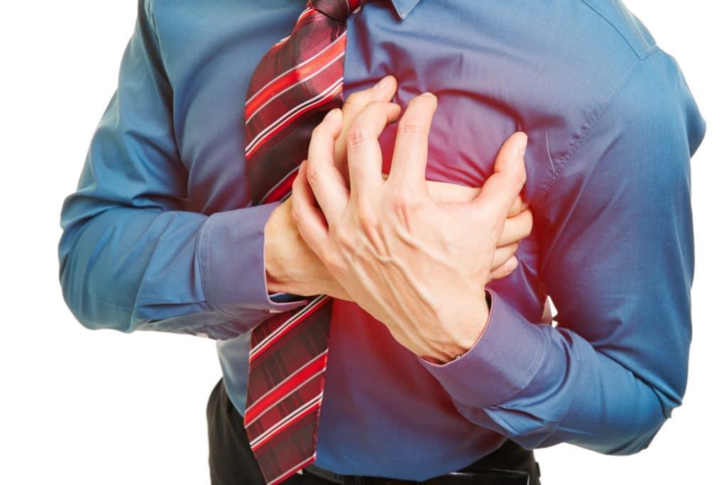 Mann mit Herzproblemen drückt Hände an Brust