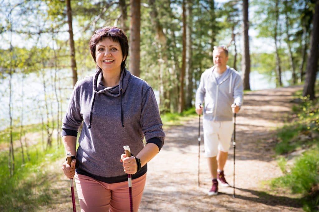 Eine Frau und ein Mann beim Nordic Walking