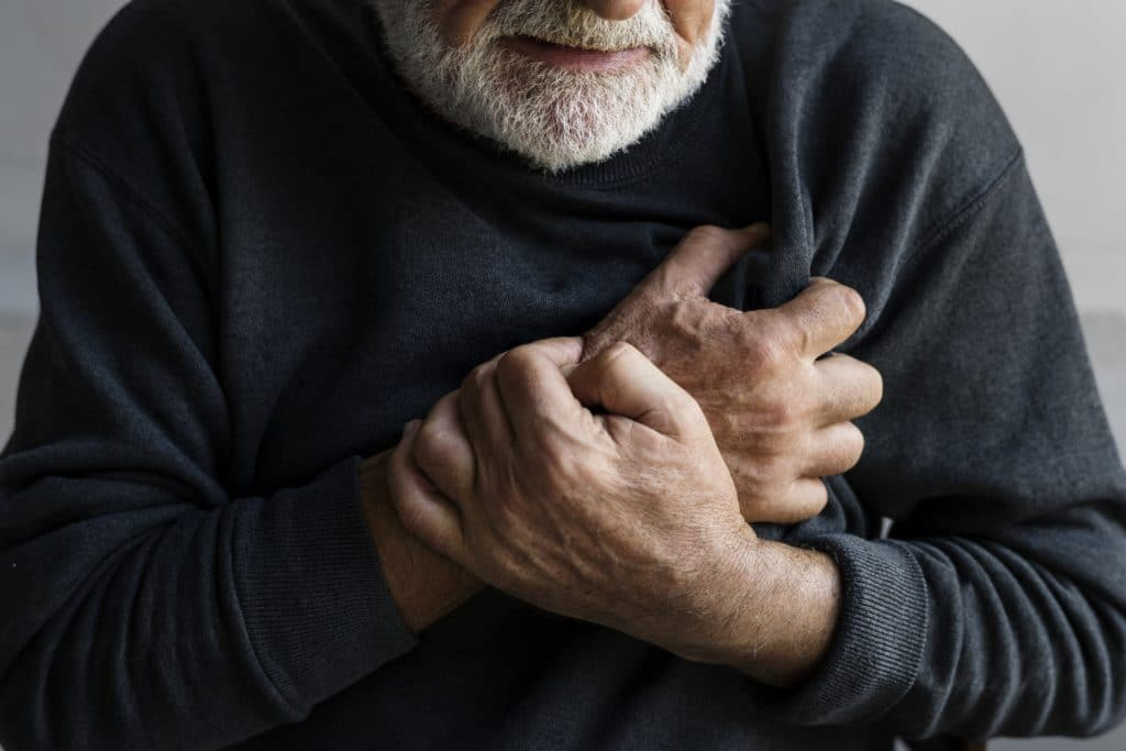Older man holds hands to his chest pain
