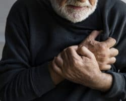 Älterer Mann hält sich die Hände an die schmerzende Brust