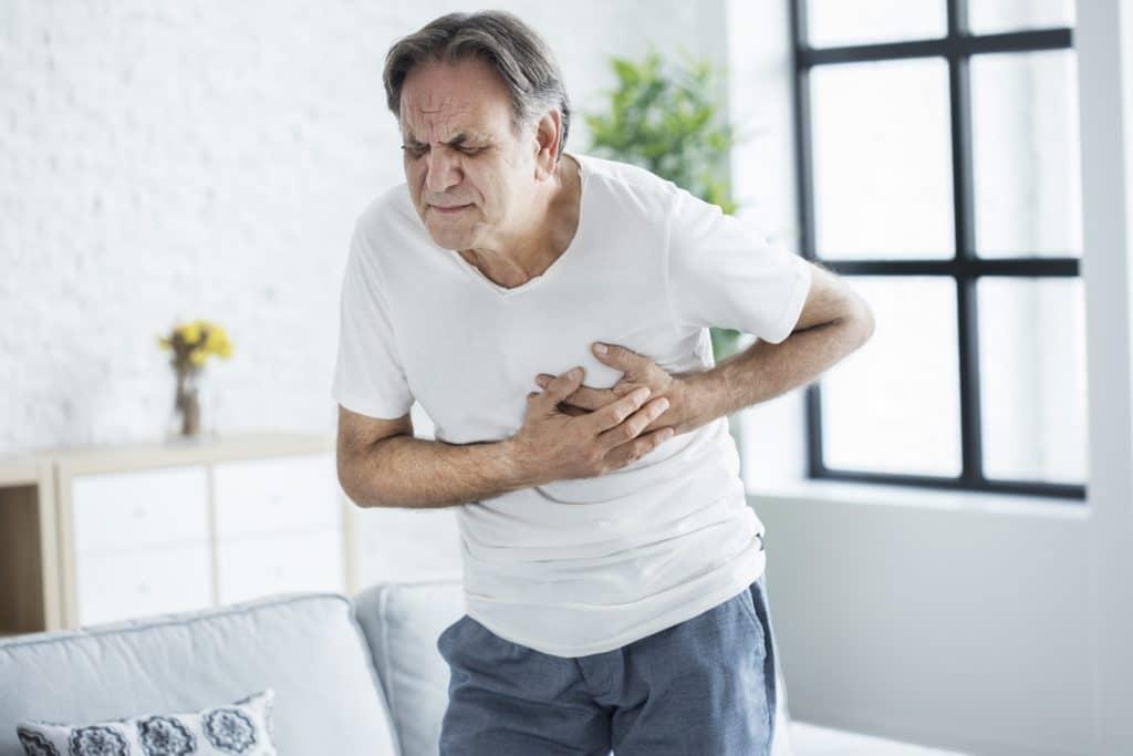 Старик держит грудь из-за сердечного приступа
