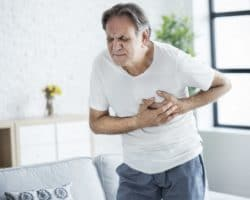 An old man is holding his chest because of a heart attack
