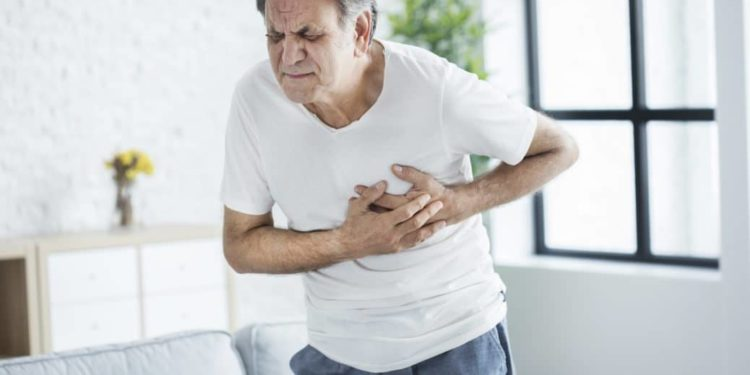 Alter Mann hält sich die Brust wegen einem Herzinfarkt
