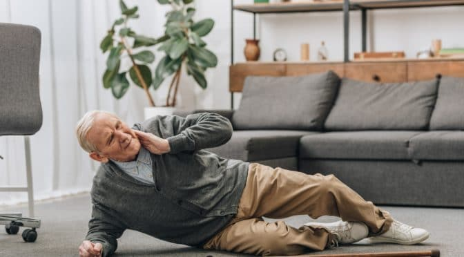 Alter Mann fiel auf den Boden und berührt seinen Nacken