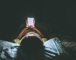 Junge Frau liegt nachts mit Smartphone im Bett