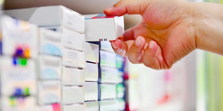 Apotheker nimmt eine Medikamentenpackung aus dem Regal