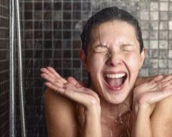 Junge Frau unter der Dusche reagiert überrascht