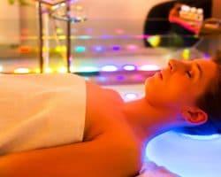 Junge Frau liegt im Handtuch auf einem farbigen Kopfkissen und diverse Farben leuchten