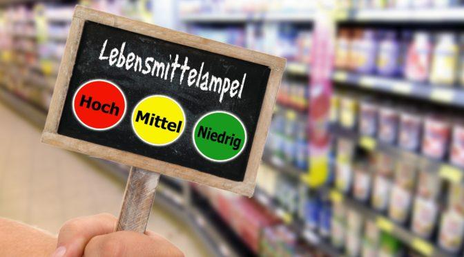 Schiefertafel mit einer Lebensmittelampel vor einem unscharfen Frischeregal im Supermarkt