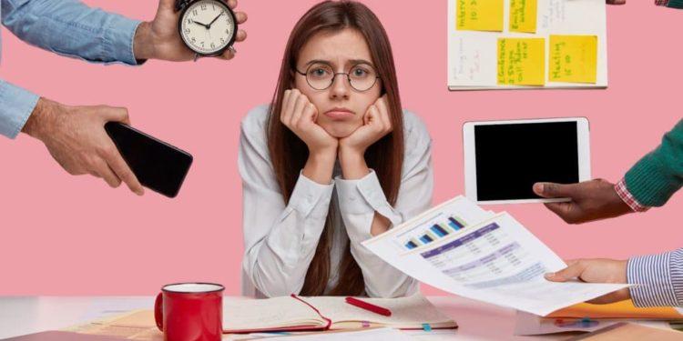 Junge Frau sitzt an vollem Schreibtisch, stützt sich mit den Armen auf, während Kollegen ihr Zettel, Ipad, Smartphone etc. hinhalten