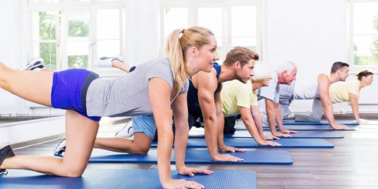Mehrere Personen kniend beim Sportkurs