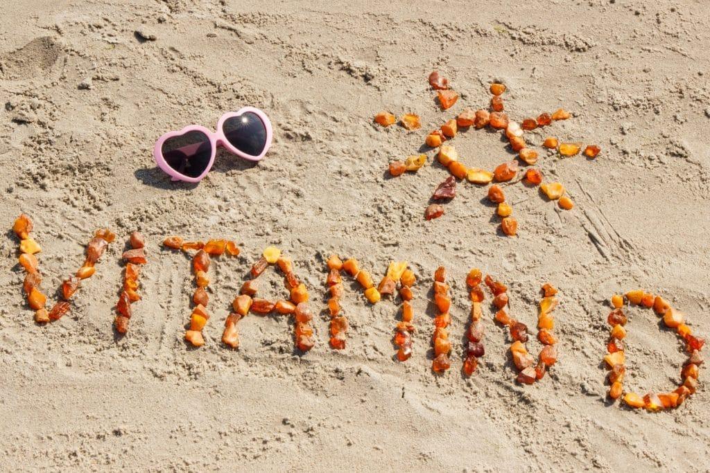 Sonnenbrille und das aus kleinen Teilen zusammengesetzte Wort Vitamin D sowie die Form einer Sonne am Strand