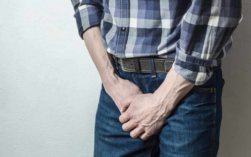 Ein Mann fasst sich an den Genitalbereich